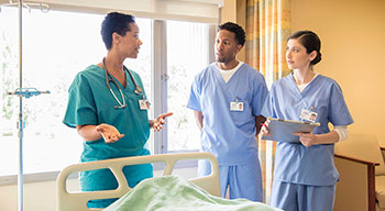 Three nurses talking at the foot end of a bed