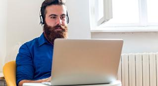 Man with a big beard wearing headphones while working on his laptop