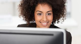 Woman smiling while looking at computer screen