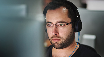 Close-up of man wearing headphones concentrating on his computer screen