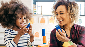 An adult woman playing blocks with a child and engaging in conversation.