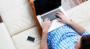 Man on sofa working on laptop with cellphone close by