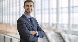 A male business professional with arms crossed confidently smiling at the camera.
