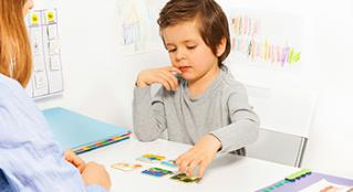 A young child working on a developmental activity with a psychologist.