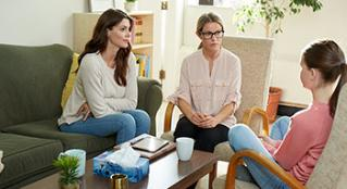 Family Counselor sitting and talking with mother and daughter