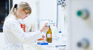 Woman in white lab coating working in lab