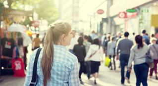 Woman with a long blonde ponytail walking through a busy city.