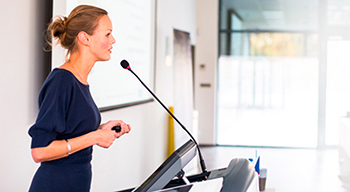 Woman standing at podium giving a presentation