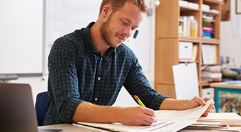 Man in a blue and green plaid shirt grading papers in his classroom.