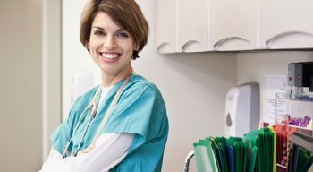 Nurse smiling and leaning on counter