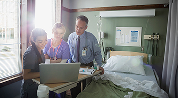 Two female nurses and a male doctor looking at a laptop in hospital room.