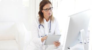 Woman wearing a white coat, glasses and a stethoscope working on her tablet