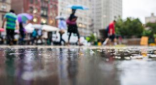 A focused shot of rain drops splashing in a puddle with a busy city street scene in the background