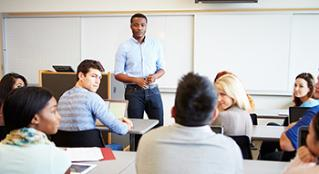A teacher standing at the front of the classroom leading class discussion with his students.