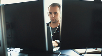 Man working in front of double monitors focused in on work.