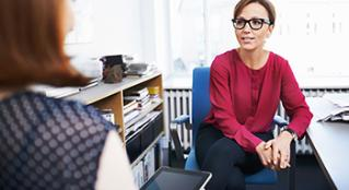 Woman wearing glasses sitting in her office talking to a colleague.