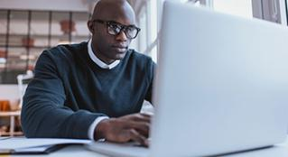 Man with thick glasses staring at laptop
